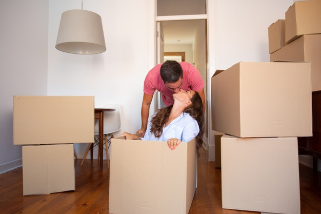 happy-young-man-dragging-box-with-his-girlfriend-inside-kissing-her_74855-10210