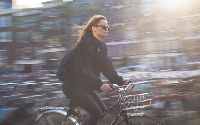 Žena v meste idúca na bicykli