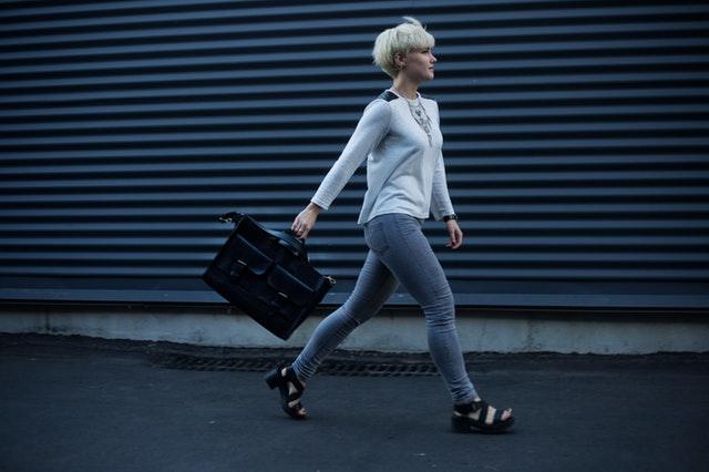 Žena s blond vlasmi, v bielom tričku a sivých nohaviciach s čiernou kabelkou kráča po ulici