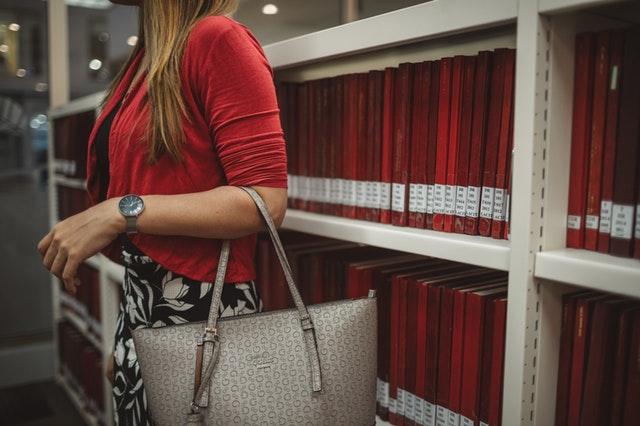 Žena v červenom saku a vzorovanej sukni s béžovou kabelkou stojí vedľa regálu s knihami
