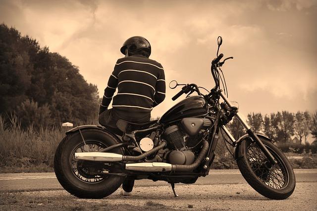 muž s prilbou pózujúci na motorke