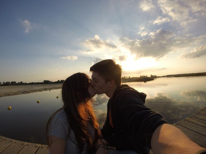 Chlapec a dievča stoja na móle pri jazere a bozkávajú sa