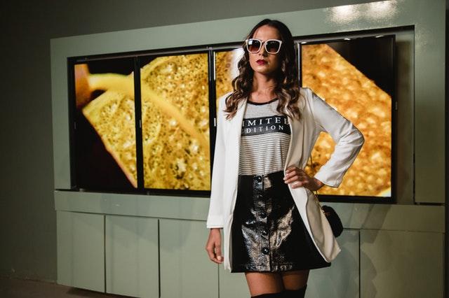 Žena v čiernej sukni, tričkom s nápisom, saku a slnečnými okuliarmi.jpg