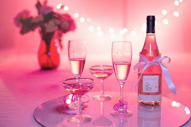 Poháre na stopke s vínom položené na stole.jpg